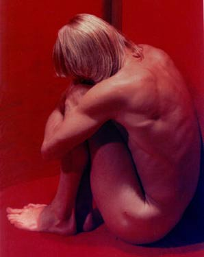 RL, nude in the corner of a red room.